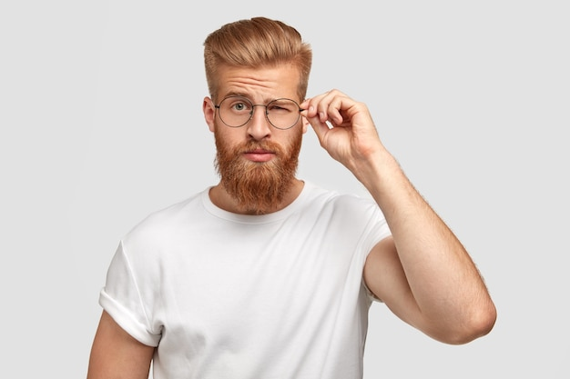 Fashionable cool man youngster with thick beard, blinks with eye, wears round spectacles