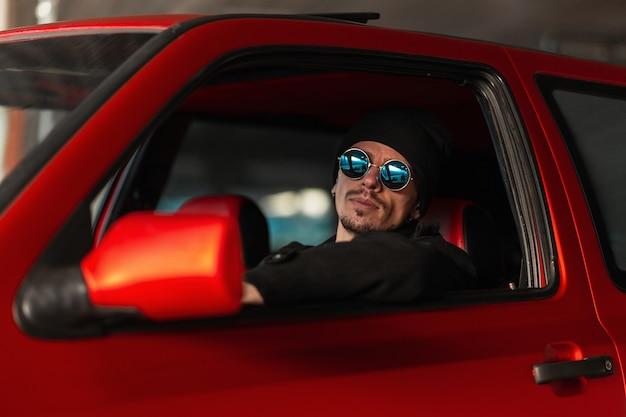 파란색 선글라스와 검은 모자를 쓴 세련된 젊은 힙스터 남자가 빨간 차를 운전하고 있다