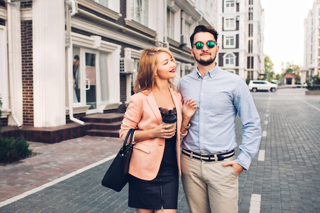 Fashionable couple is walking on street in city. handsome bearded guy in sunglasses is hugging girl and looks far away.