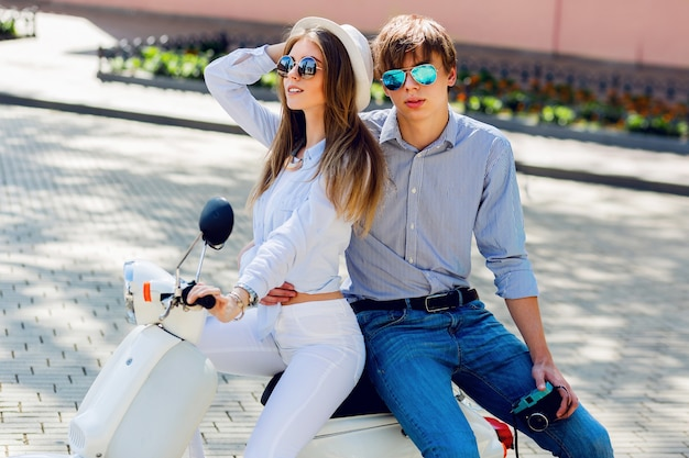 Fashionable couple posing on the street, siting on scooter
