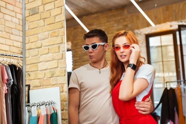 Модная пара. довольно привлекательная пара в модных солнцезащитных очках и глядя на свое отражение в зеркале магазина