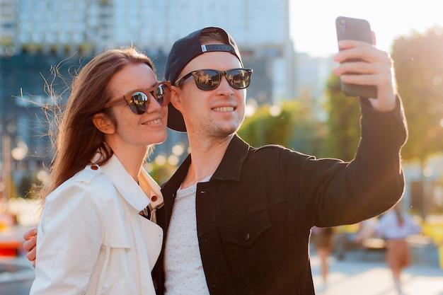 携帯電話で自分撮りをしているファッショナブルなカップル。サングラスをかけた男女が街で友達と出会い、スマートフォンで夕日を背景に写真をデート。
