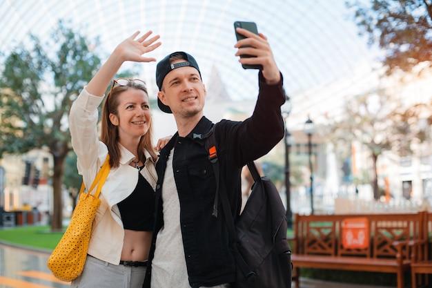 携帯電話で自分撮りをしているファッショナブルなカップル。スマートフォンで街のデートの写真で友達に会うサングラスの男と女