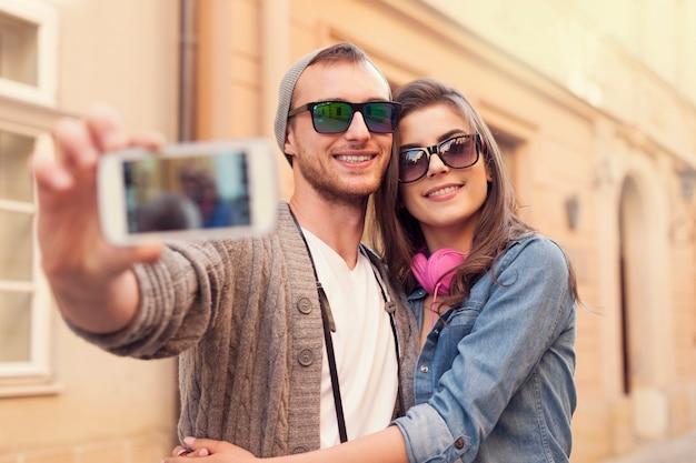 携帯電話で自分撮りをするファッショナブルなカップル