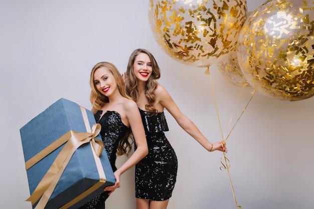 Модные кудрявые европейские девушки танцуют с воздушными шарами за белокурой подругой. крытый фото радостной молодой женщины, держащей подарок, украшенный лентой и нежно улыбаясь.