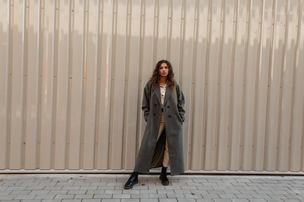패션 핸드백이 달린 빈티지 롱 코트를 입은 세련된 곱슬머리 소녀는 도시의 현대적인 금속 벽 근처에 서 있습니다. 어반 페미닌 스타일