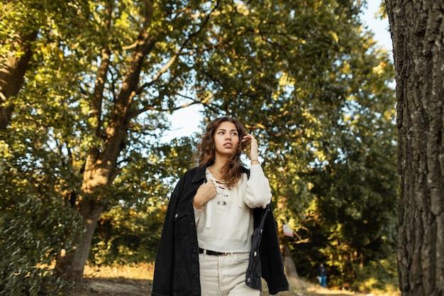 세련된 캐주얼 가을 데님 옷을 입은 세련된 곱슬머리 소녀가 시골의 자연을 걷는다