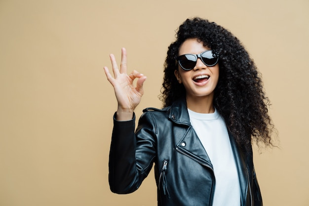 Fashionable curly haired woman tells all is fine, makes okay gesture