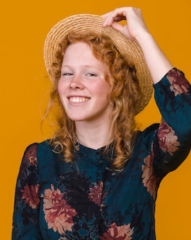 Fashionable curly redhead woman in studio with colored background