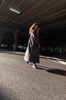 빈티지 긴 코트를 입은 세련된 곱슬머리 여성은 화창한 날 도시를 산책합니다. 어반 페미닌한 스타일과 아름다움