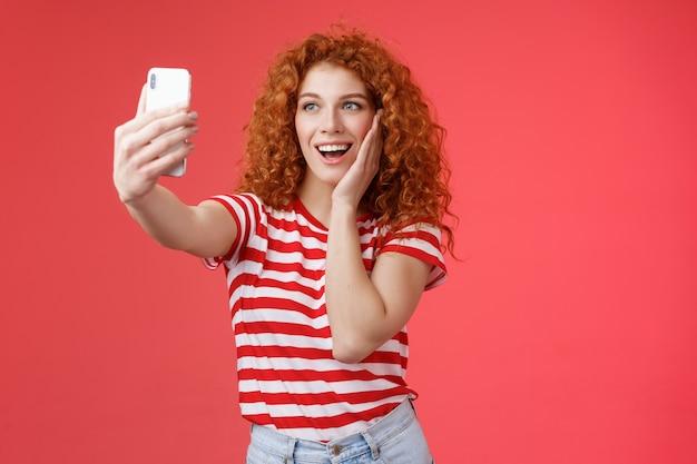 Модная милая рыжая кудрявая женская летняя футболка записывает видео в социальных сетях из роскошных тропических путешествий за границу, снимает селфи, удерживая смартфон, позу глупой фотографии на красном фоне.