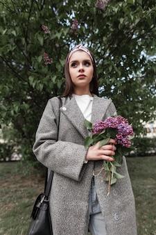 세련된 코트를 입은 빈티지 반다나를 입은 세련된 귀여운 여성은 화창한 날 거리에 꽃다발 라일락을 들고 서 있습니다. 보라색 꽃을 가진 사랑스러운 매력적인 소녀 모델이 야외에서 산책합니다. 봄 자연의 아름다움입니다.