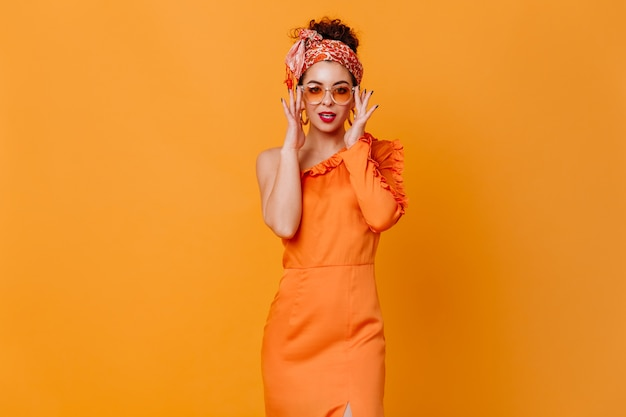 Fashionable dark-haired lady in headband in african style, sunglasses and elegant dress coquettishly looks into camera on orange space.