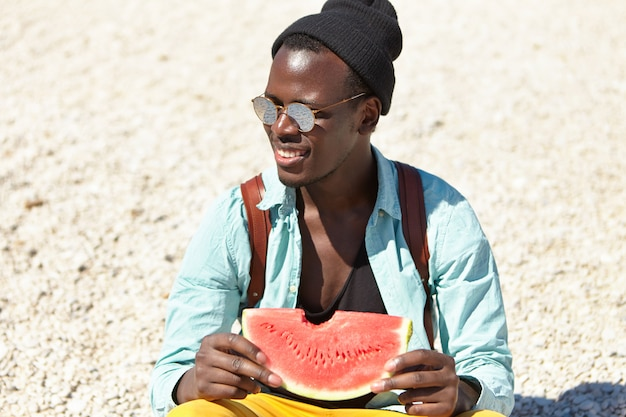 Fashionable dark-skinned young european male student in stylish sunglasses and headwear relaxing on city beach, holding fresh watermelon, quenching his thirst on hot sunny day after university