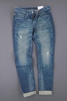 Модные джинсовые брюки на сером фоне, вид сверху