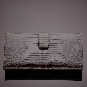 Fashionable designer leather wallet on a brown background