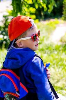 旅行中に彼の肩の後ろにバックパックを持つファッショナブルな服を着た男の子
