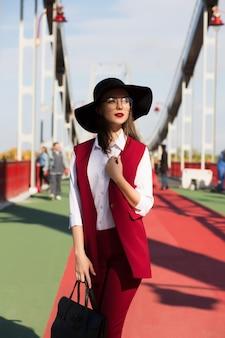 晴れた日に橋でポーズをとる赤いパンツスーツと黒い帽子のファッショナブルな服を着たブルネットモデル