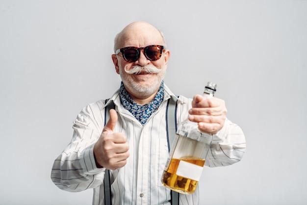 Модный пожилой мужчина держит бутылку хорошего алкоголя. зрелые старшие, чувак