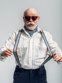 Fashionable elderly man in trousers with suspenders and sunglasses. mature senior, dude