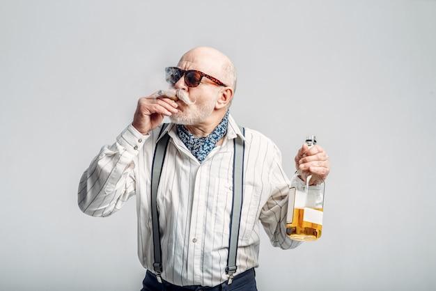 Модный пожилой мужчина с сигарой и бутылкой хорошего алкоголя. зрелые старшие, чувак
