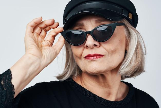 Модная пожилая женщина в солнцезащитных очках позирует крупным планом