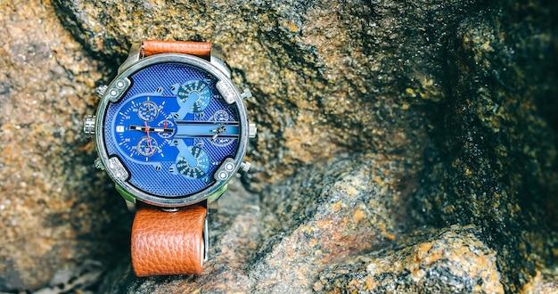 야외에서 돌 위에 누워 있는 세련된 우아한 남성용 시계. 자연 숲의 세련된 액세서리. 공간 장소를 복사합니다. 여행 나침반, 바위에서의 모험.