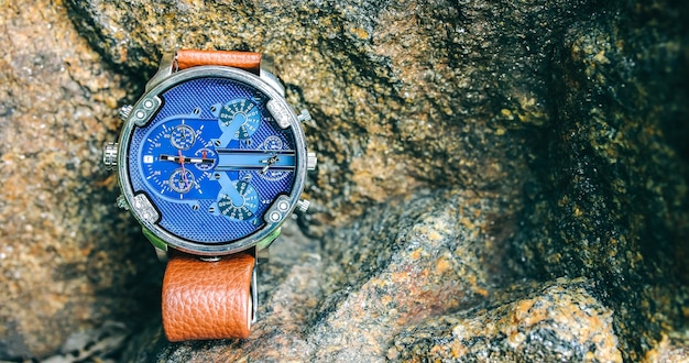 Fashionable elegant men's watch lying outdoors on the stone. stylish accessories in the nature forest. copy space place. travel compass, adventure in the rocks.