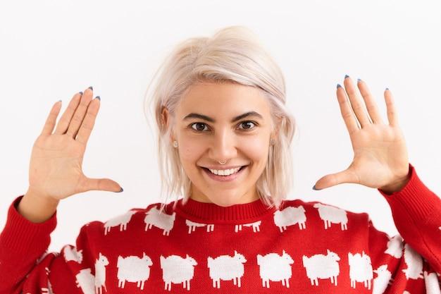 염색 된 분홍빛이 도는 머리를 가진 유행 감정적 인 젊은 여자는 흥분된 표정 데 그녀의 얼굴에 손을 잡고 절연 제스처를 만드는 포즈. 젊음, 재미 있고 긍정적 인 감정