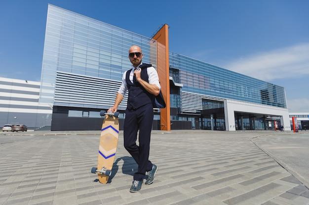 完璧なスイートでファッショナブルなヨーロッパのビジネスマンが通りを歩く