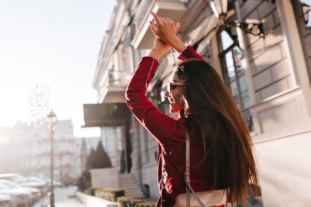 晴れた日に町を探索する長い黒髪のファッショナブルなヨーロッパの女性