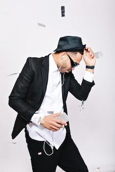 Ragazzo bello eccitato alla moda in vestito, cappello, occhiali da sole neri divertendosi in orpelli. ascoltare la musica attraverso le cuffie, ballare, celebrare la festa, figo.