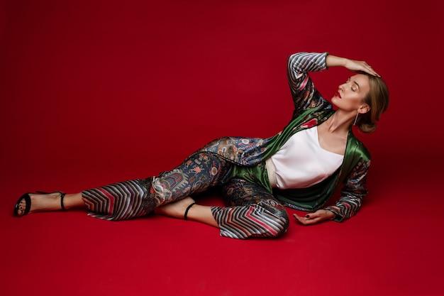 Модная светловолосая дама в ярком шелковом костюме и элегантных босоножках