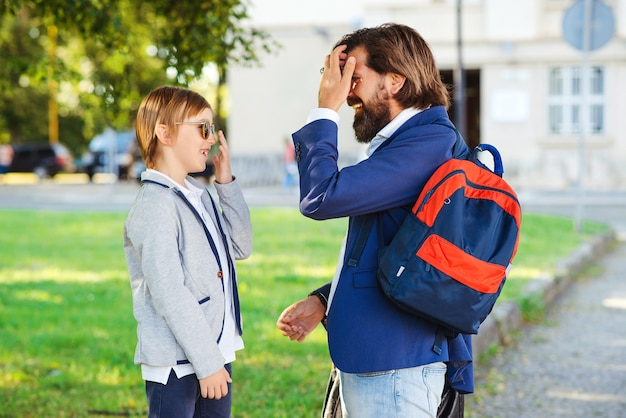Fashionable father takes child to school. back to school concept.
