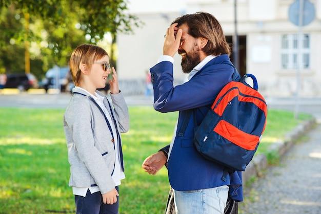 Модный отец водит ребенка в школу. снова в школу концепции.