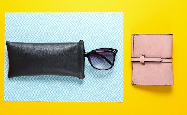 Модные женские аксессуары на бумажном фоне. модные кожаные кошельки, солнцезащитные очки в защитном футляре. вид сверху