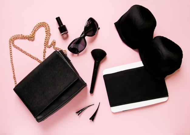 Модные женские аксессуары на мягком розовом фоне. клатч, солнцезащитные очки, лак для ногтей, бюстгальтер, кисть для макияжа, спрей, булавки и прочее.
