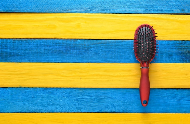 Fashionable female comb for hair care on a yellow blue wooden table. trend of minimalism. copy space. top view. summer concept.