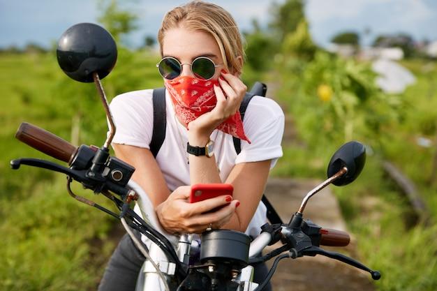 Driver femminile alla moda vestito casualmente, legge il blog dei motociclisti sul cellulare, si siede sulla moto, rinfresca l'aria fresca all'aperto, guarda pensieroso in lontananza. persone, stile di vita e tecnologia