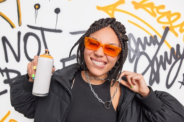 Fashionable female teenager bites lips holds chain holds aerosol spray makes creative drawings in public place has urban style dreadlocks hairstyle poses on graffiti wall