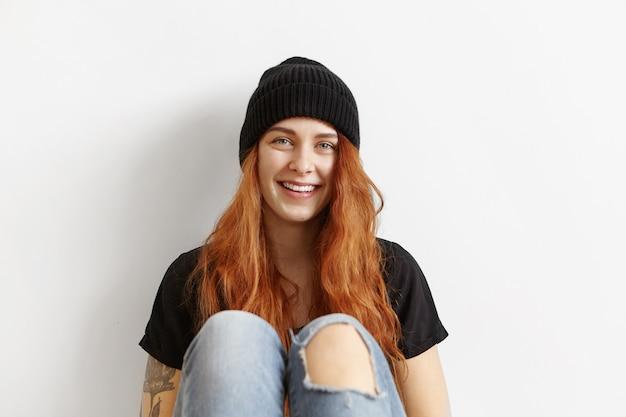 Модная девушка-подросток с растрепанными рыжими волосами расслабляется в помещении