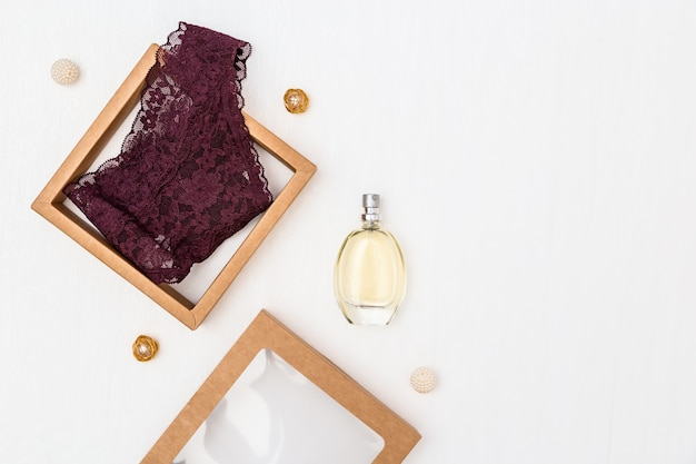 Fashionable female underwear, maroon woman panty in gift box, glass bottle with perfume.