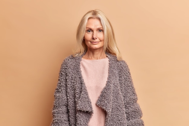 Fashionable fifty years old woman with blonde hair dressed in jumper and warm coat looks directly at front with serious expression poses against beige wall stays beautiful in any age