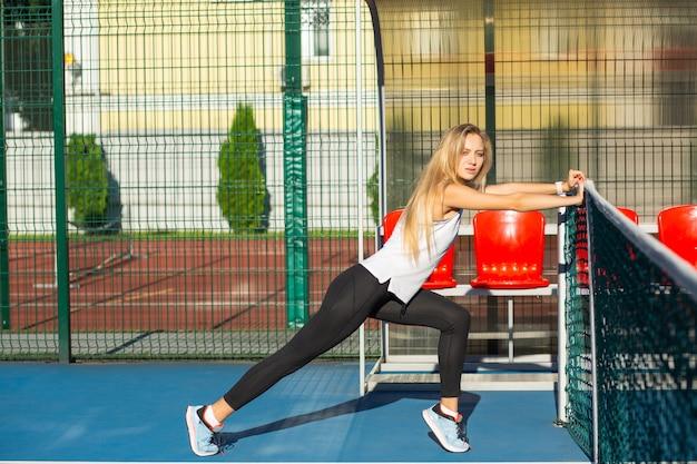 테니스 코트에서 운동하기 전에 스트레칭을 하는 세련된 금발 모델, 야외 촬영