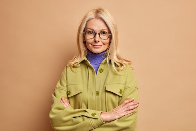 Fashionable forty years old blonde woman stands in assertive pose keeps hands crossed wears transparent glasses and autumn coat.