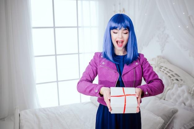유행 괴물. 파란 머리를 가진 아름 다운 여자를 놀라게 매력적인 흰색 침실에서 선물을 들고있다. 패션과 뷰티 개념