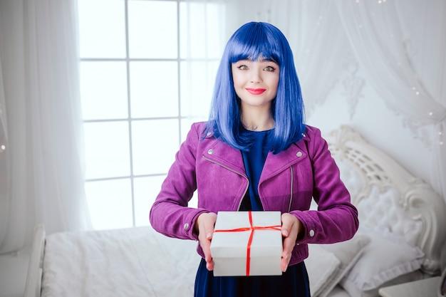 유행 괴물. 파란 머리를 가진 매력적인 웃는 아름 다운 여자의 초상화는 흰색 침실에서 선물을 들고있다. 패션과 뷰티 개념