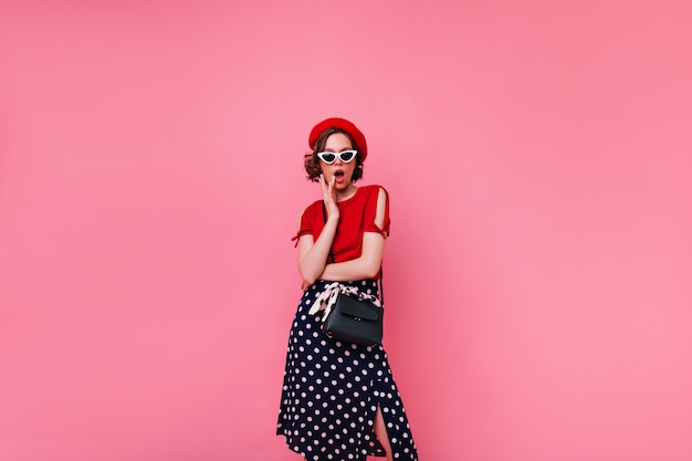 Fashionable french girl in long black skirt posing. enchanting short-haired woman in beret standing.