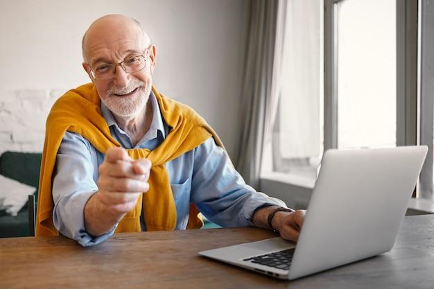 Reclutatore maschio anziano amichevole alla moda che indossa occhiali rettangolari e abiti eleganti che lavora su computer portatile, sorride ampiamente e punta il dito, scegliendoti per la posizione di lavoro