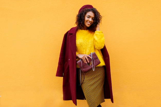Fashionable girl in amazing winter outfit and accessories posing on yellow.